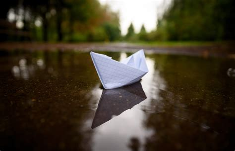 Paper boat floating on water in autumn park   Edwards